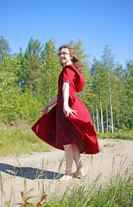Viininpunaista kietaistavaa mekkoa voi käyttää myös liivinä. Yksityiskohdat päällystettyjä nappeja ja vuoritettua huppua myöten ovat Marimekon Kurjenpolvea.